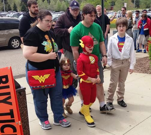 Description of . Mark and Jenny Swerbensky walk into the 2014 Motor City Comic Con with their children, Xander, 11, dressed as Superman, Aiden, 7, dressed as The Flash, and Emily, 3, dressed as Wonder Woman. Photo by David Komer.