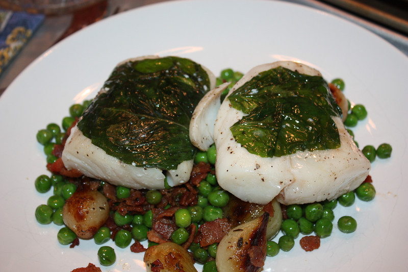 "Black Bream with Basil & Peas ""Bonne Femme"" (by Gordon Ramsay from his book ""Family Fare"")<br /> <br /> INGREDIENTS (for 6):<br /> 6 black bream fillets, skin on, about 6oz each<br /> sea salt and freshly ground black pepper<br /> smal handful of basil leaves<br /> olive oil, to drizzle<br /> <br /> PEAS ""BONNE FEMME"":<br /> olive oil, for cooking<br /> 9oz unsmoked bacon, cut into small cubes<br /> 5oz pearl onions, peeled<br /> few thyme sprigs, leaves only<br /> 1 1/3 lb fresh or frozen peas (thawed, if frozen)<br /> <br /> DIRECTIONS:<br /> Check the fish for small bones, removing any that you find with tweezers.  Score the skin at 1/2-inch intervals.  Season with salt and pepper and place a few basil leaves on the flesh side.  Place each bream fillet on a large piece of plastic wrap and drizzle with olive oil.  Wrap up to enclose the fillets in the plastic wrap, twisting the ends tightly to seal.<br /> <br /> For the peas, heat a little olive oil in a skillet and cook the bacon for 8 to 10 minutes until golden brown and crisp.  Remove and drain on paper towels.  Add the onions and thyme to the pan and cook on medium heat, stirring occasionally, for 10 minutes until the onions are tender.<br /> <br /> In the meantime, bring a large pan of water to a boil, then reduce the heat to a low simmer.  Add the wrapped bream fillets and gently poach for about 10 minutes until the fish is opaque and cooked through.  If the center is not cookd through, poach for another 2 to 3 minutes.<br /> <br /> Add the peas and bacon to the onions and cook for 2 to 3 minutes until the peas are tender.  Season well.<br /> <br /> Divide the peas ""bonne femme"" among six warm plates.  Unwrap the bream fillets and place on top of the vegetables, skin side up.  Drizzle with a little olive oil and sprinkly with sea salt.  Serve immediately.<br /> <br /> JOHN'S NOTES:<br /> The only thing I really did any different here was use frozen cod fillets (skin off) rather than the skin on fish (it's what we had)."