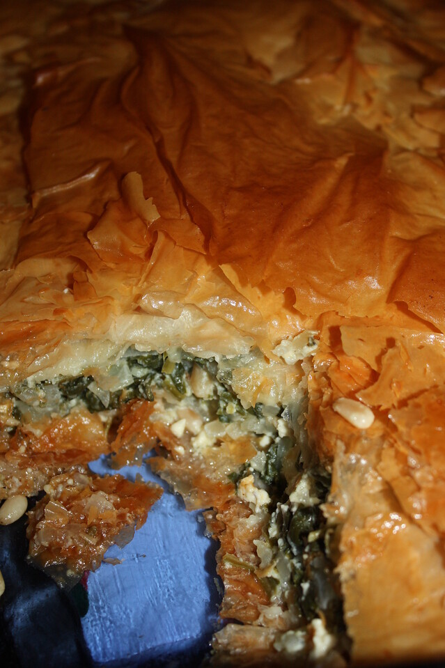 """Spanakopita (from Gordon Ramsay's book """"World Kitchen"""")<br /> <br /> INGREDIENTS:<br /> 2 tbsp olive oil<br /> 2 large sweet onions, peeled and minced<br /> sea salt and black pepper (we used Kosher salt)<br /> 1 lb spinach leaves, washed and drained<br /> nutmeg, to grate<br /> 9 oz feta, crumbled<br /> 2 large eggs<br /> generous 1/2 cup heavy cream<br /> scant 1/2 cup pine nuts, toasted<br /> scant 1/2 cup butter, melted<br /> 14 sheets of phyllo pastry<br /> <br /> DIRECTIONS:<br /> Heat the olive oil in a skillet over medium heat and add the onions with a little salt and pepper.  Cook, stirring frequently, for 6 to 8 minutes until soft but not colored.  Transfer to a large bowl.<br /> <br /> Wilt the spinach leaves in several batches: stir them in a large saucepan over medium-high heat until just wilted, then tip into a colander.  Press down on the spinach with the back of a ladle to squeeze out as much excess water as possible.  Allow to cool slightly, then chop roughly.<br /> <br /> Add the spinach to the onion and grate over a little nutmeg.  Add the feta, eggs, and cream.  Season with a generous grinding of pepper and just a small pinch of salt - as the feta is salty.  Finally, stir in the pine nuts.  Chill until ready to use.<br /> <br /> Preheat the oven to 400F.  Brush the base of a large ovenproof dish with a little of the melted butter.  Now layer 10 sheets of phyllo pastry in the dish, brushing each layer with butter and allowing any excess to overhand the sides.  Spoon the spinach and feta mix over the pastry sheets and then fold any overhanging phyllo over the filling.  Layer the remaining phyllo sheets on top, buttering generously and scrunching for an attractive finish.<br /> <br /> Bake in the oven for 50 to 60 minutes until the top of the pie is golden and the filling is set.  To check, insert a small knife into the center of the pie - the filling should not look too runny.<br /> <br /> Let stand for at least 10 minutes before slicing.  Serve th"""