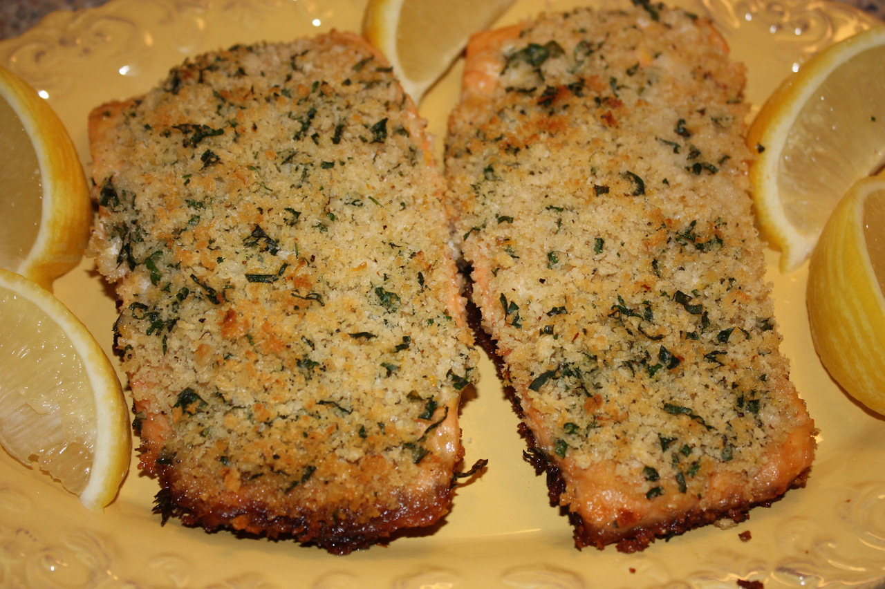 """Panko-crusted Salmon by Ina Garten from her book """"Barefoot Contessa: How Easy is That?""""<br /> <br /> INGREDIENTS:<br /> 2/3 cup panko (Japanese dried bread flakes)<br /> 2 tablespoons minced fresh parsley<br /> 1 teaspoon grated lemon zest<br /> Kosher salt and freshly ground black pepper<br /> 2 tablespoons good olive oil<br /> 4 (6- to 8-ounce) salmon fillets, skin on<br /> 2 tablespoons Dijon mustard<br /> 2 tablespoons vegetable oil<br /> Lemon wedges, for serving<br /> <br /> DIRECTIONS:<br /> Preheat the oven to 425 degrees.<br /> <br /> In a small bowl, mix together the panko, parsley, lemon zest, 1/2 teaspoon salt, and 1/2 teaspoon pepper.  Drizzle with the olive oil and stir until the crumbs are evenly coated.  Set aside.<br /> <br /> Place the salmon fillets, skin side down, on a board.  Generously brush the top of the fillets with mustard and then sprinkle generously with salt and pepper.  Press the panko mixture thickly on top of the mustard on each salmon fillet.  The mustard will help the panko adhere.<br /> <br /> Heat the vegetable oil over medium-high heat in a 12-inch cast-iron skillet or large heave, ovenproof pan.  When the oil is very hot, add the salmon fillets, skin side down, and sear for 3 to 4 minutes, without turning, to brown the skin.<br /> <br /> Transfer the pan to the hot oven for 5 to 7 minutes until the salmon is almost cooked and the panko is browned.  Remove the oven, cover with aluminum foil, and allow to rest for 5 to 10 minutes.  Serve the salmon hot or at room temperature with lemon wedges."""
