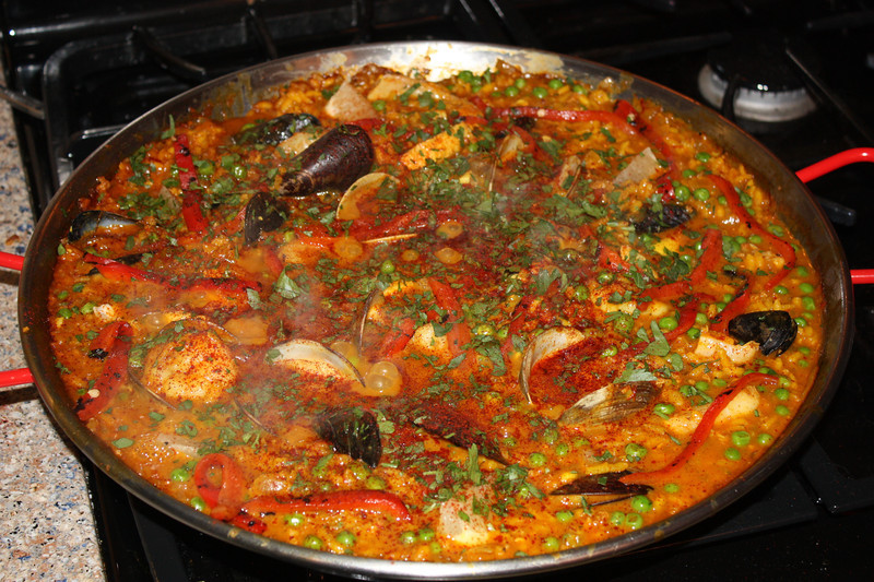 "Seafood Paella (by Eric Ripert from the series ""Avec Eric"" on PBS)<br /> <br /> INGREDIENTS:<br /> <br /> 1/4 cup extra virgin olive oil<br /> 1/4 pound chorizo, sliced ¼-inch thick<br /> 1 onion, chopped<br /> 6 garlic cloves, chopped<br /> 1/2 tablespoon saffron<br /> 1 teaspoon turmeric<br /> 3 cups short grain rice<br /> 8 cups chicken stock<br /> -Kosher Salt<br /> -fresh ground black pepper<br /> 2 dozen cockles, scrubbed<br /> 1 pound mussels, rinsed and beards removed<br /> 1 pound striped bass fillet, cut into 8 pieces<br /> 18 large shrimp, peeled and deveined<br /> 2 cups green peas<br /> 1 red pepper, roasted, peeled and cut into ¼-inch julienne<br /> 1/4 cup chopped parsley<br /> - paprika<br /> 1 lemon, cut into 8 wedges<br /> <br /> DIRECTIONS:<br /> Place an 18-inch paella pan over medium-high heat. Add the olive oil. When the oil is hot, add chorizo and render the sausage. Add the saffron and cook down.  Add the onions, garlic and turmeric and sweat until just softened. Add the rice, stir to coat and lightly toast the rice for about 3 minutes.<br /> <br /> Add some of the chicken stock and stir to combine. Season with salt and pepper.  Cook for 15 minutes adding more chicken stock as necessary to keep the rice moist. Add the mussels and cockles with the hinge sides down, so they can easily open.  Add the striped bass and the shrimp, making sure each piece is slightly buried in the rice.  Add the peas and work in with a fork.  Cook the paella for another 4 to 5 minutes until the shrimp and fish start to turn opaque.  (Use a fork to flip them if necessary.)   Place the peppers around the pan like spokes on a bicycle. Cover with foil and continue cooking for another 5 minutes or until the mussels and clams open.<br /> <br /> Uncover and sprinkle with chopped parsley, paprika and serve immediately with lemon wedges.<br /> <br /> JOHN'S NOTES:<br /> So, the short grain rice usually used in paella is Boma rice.  Couldn't find it, so used arborio rice (risotto rice).  Fitting as the dish start just like a risotto with toasting the rice before adding the liquid - and adding just enougn to keep the rice moist.<br /> <br /> Also, couldn't find cockles, so used littleneck clams."