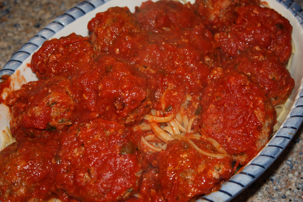 """Spicy Turkey Meatballs & Spaghetti (by Ina Garten from her book """"barefoot contessa - how easy is that?"""")<br /> <br /> INGREDIENTS:<br /> 3 cups (1-inch diced) bread cubes from a round rustic bread, crusts removed<br /> 2/3 cup whole mile<br /> 2 pounds ground turkey (85% to 92% lean)<br /> 1/2 pound sweet Italian pork sausage, casings removed<br /> 4 ounces thinly sliced prosciutto, finely chopped<br /> 1 cup freshly grated aged Asiago cheese<br /> 1/2 cup minced fresh parsley<br /> 1 teaspoon dried oregano<br /> 1 teaspoon crushed red pepper flakes<br /> Kosher salt and freshly ground black pepper<br /> 3 tablespoons good olive oil, plus extra for brushing the meatballs<br /> 2 extra-large eggs, lightly beaten<br /> 3 (24-ounce) jars good marinara sauce<br /> 2 pounds dried spaghetti<br /> Freshly grated Parmesan cheese, for serving<br /> <br /> DIRECTIONS:<br /> 1.  Preheat the oven to 400 degrees.  Line 2 sheet pans with parchment paper.<br /> <br /> 2.  Place the bread in the bowl of a food processor fitted with the steel blade.  Process untili the bread is in medium crumbs.  Transfer the crumbs to a small bowl and add the milk.  Set aside for 5 minutes.<br /> <br /> 3.  In a large mixing bowl, combine the turkey, sausage, prosciutto, bread mixture, Asiago, parsley, oregano, red pepper flakes, 1 tablespoon salt, and 1 1/2 teaspoons pepper.  Lightly combine the ingredients with your hands.  Add the 3 tablespoons of olive oil and the eggs, and stir lightly with a fork to combine.<br /> <br /> 4.  With your hands, lightly roll the mixture into 2-inch round meatballs and place them on the prepared sheet pans.  Brush the meatballs with olive oil.  Bake for 35 to 40 minutes, until the tops are browned and the centers are completely cooked.<br /> <br /> 5.  Pour the marinara sauce in a large, low pot, add the meatballs, and bring to a simmer.<br /> <br /> 6.  Meanwhile, cook the spaghetti in a large pot of boiling salted water according to the directions on the package"""