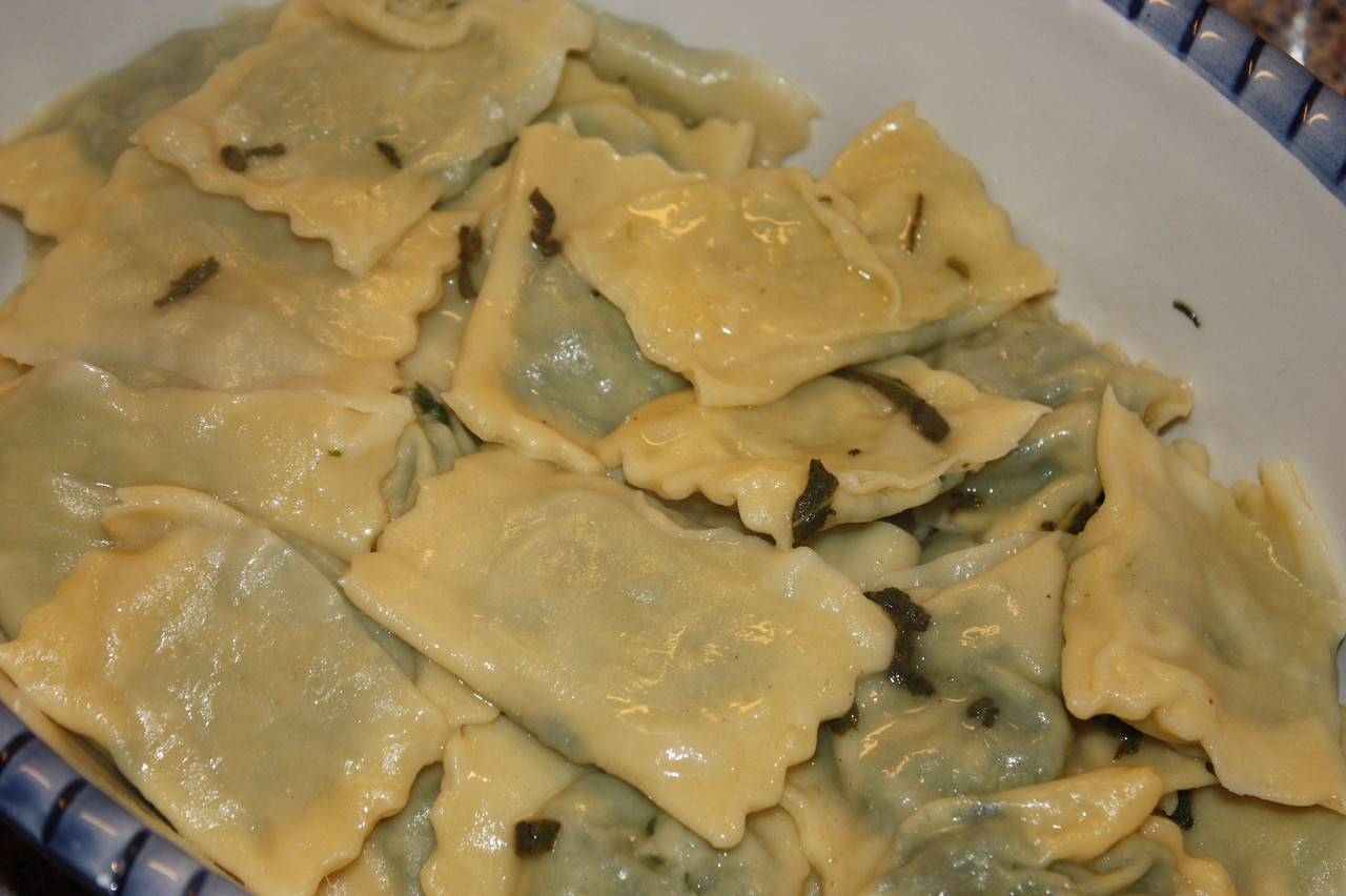"""Spinach, Ricotta and Pine Nut Ravioli with Sage Butter (by Gordon Ramsay from the iPhone app """"Gordon Ramsay Cook With Me"""")<br /> <br /> INGREDIENTS:<br /> For the pasta dough:<br /> Italian '00' flour (1lb 4 oz)<br /> 1/4 tsp fine sea salt<br /> 4 medium eggs<br /> 6 eggs (yolk only)<br /> 2 tbsp olive oil<br /> <br /> For the egg wash:<br /> 1 egg (yolk only)<br /> <br /> For the filling:<br /> 1/2 oz butter<br /> 2 garlic cloves<br /> 1 lb fresh baby spinach (leaves only)<br /> 1/4 tsp nutmeg (freshly grated)<br /> 5oz ricotta<br /> 2 1/2 oz Parmesan<br /> 2 1/2 oz toasted pine nutes<br /> 1 lemon (zest only)<br /> <br /> For the sage butter<br /> 2 1/2 oz unsalted butter<br /> 6 sprigs fresh sage leaves<br /> lemon (juice only, to taste)<br /> <br /> To serve:<br /> Parmesan<br /> <br /> You will also need<br /> olive oil<br /> salt and freshly ground black pepper<br /> <br /> DIRECTIONS:<br /> 1.  TO make the filling, heat the olive oil in a large frying pan, add butter.  Finely chop the garlic and fry until lightly golden.<br /> 2.  Add the spinach and cook for 2-3 minutes, until the liquid has released and been absorbed.<br /> 3.  Increase the heat slightly and add nutmeg and seasoning.  Squeeze out any excess water and roughly chop the spinach.<br /> 4.  In a large bowl, beat together the ricotta, grated Parmesan and toasted pine nuts.  Stir in the spinach and lemon zest.  Taste and adjust the seasoning if necessary, then cover and chill for at least 30 minutes.<br /> 5.  For the pasta, put all the ingedients into a food processor and whizz until the mix resembles coarse crumbles.<br /> 6.  Tip onto a floured work surgace and press into a ball with your hands.<br /> 7.  Knead until smooth.  The dough should be soft but not sticky; if it feels wet, knead in a little more flour.  Wrap in cling film and chill for 30 minutes.<br /> 8.  Cut the pasta into 8 pieces, roll into balls and keep each wrapped until needed.<br /> 9.  Using a pasta machine, roll each ball """