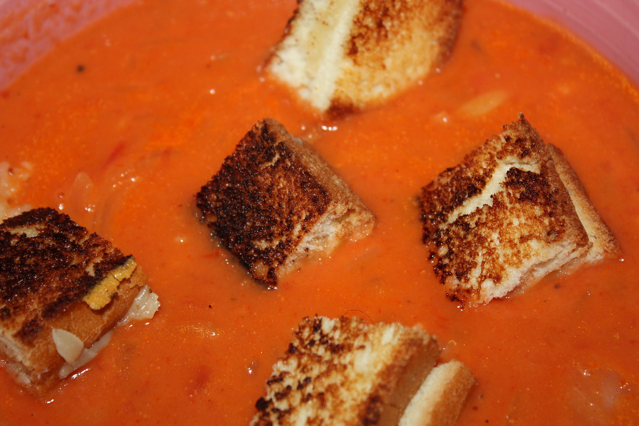 """Easy Tomato Soup and Grilled Cheese Croutons (from Ina Garten's amazing book, """"barefoot contessa: Foolproof"""")<br /> <br /> Ingredients<br />     3 tablespoons good olive oil<br />     3 cups yellow onions, chopped (2 onions)<br />     1 tablespoon minced garlic (3 cloves)<br />     4 cups chicken stock, preferably homemade<br />     1 (28-ounce) can crushed tomatoes, preferably San Marzano<br />     Large pinch of saffron threads<br />     Kosher salt and freshly ground black pepper<br />     1/2 cup orzo<br />     1/2 cup heavy cream<br />     Grilled Cheese Croutons (see below)<br /> <br /> Directions<br /> <br /> In a large pot or Dutch oven such as Le Creuset, heat the olive oil over medium heat. Add the onions and cook over medium-low heat for 15 minutes, stirring occasionally, until golden brown. Add the garlic and cook for 1 more minute. Stir in the chicken stock, tomatoes, saffron, 1 tablespoon salt and 1 teaspoon pepper. Bring the soup to a boil, then lower the heat and simmer for 15 minutes.<br /> <br /> Meanwhile, fill a medium pot with water, add 2 teaspoons salt and bring to a boil. Add the orzo and cook for 7 minutes. (It will finish cooking in the soup.) Drain the orzo and add it to the soup. Stir in the cream, return the soup to a simmer and cook for 10 more minutes, stirring frequently.<br /> <br /> Serve hot with Grilled Cheese Croutons scattered on top.<br /> <br /> Grilled Cheese Croutons<br /> <br /> 4 (1/2-inch-thick) slices country white bread<br /> <br /> 2 tablespoons unsalted butter, melted<br /> <br /> 4 ounces Gruyere cheese, grated<br /> <br /> Heat a panini grill. Place the four slices of bread on a cutting board and brush lightly with the melted butter, being sure to butter the corners. Turn the slices over and pile Gruyere on two of the slices. Place the remaining two slices of bread on top of the Gruyere, buttered sides up.<br /> <br /> Grill the sandwiches on the panini grill for about 5 minutes, until nicely browned. Place on a cut"""