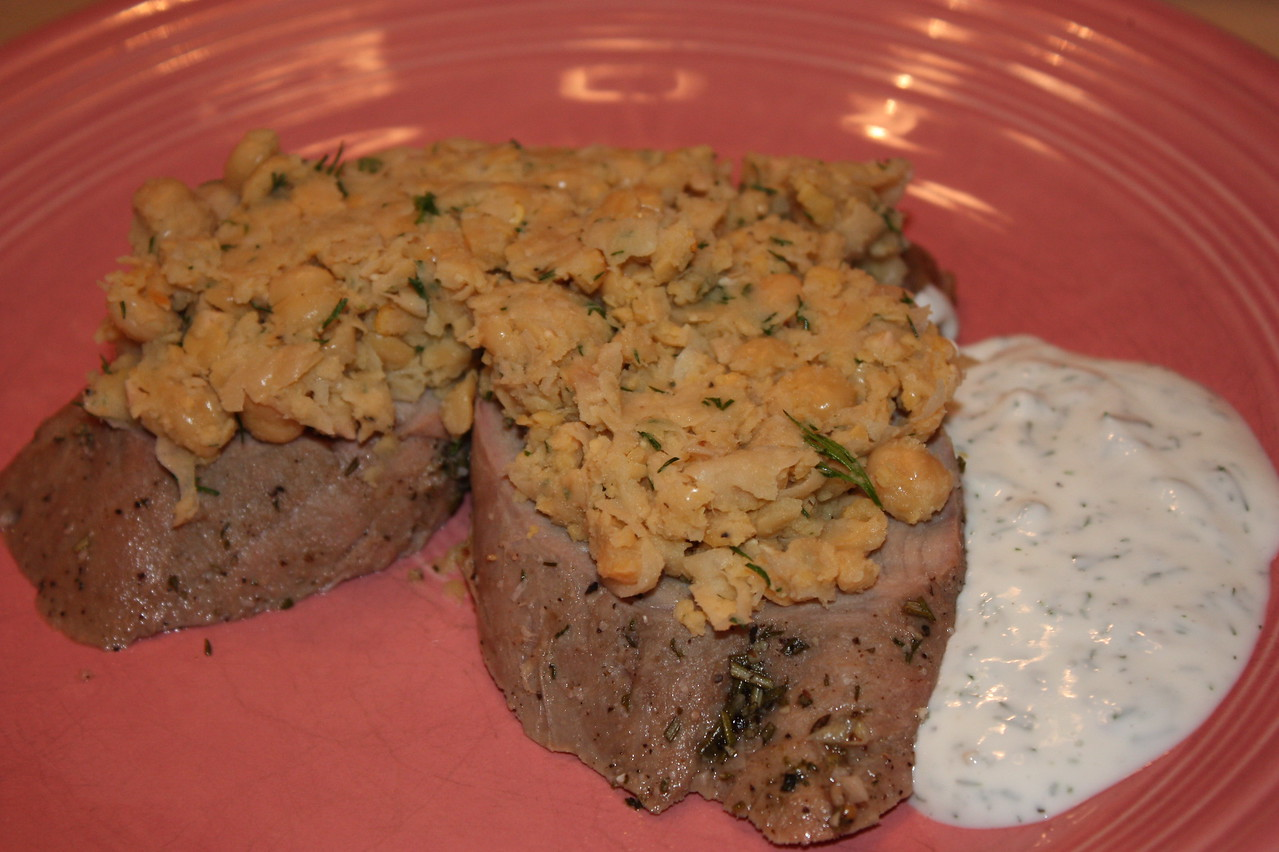 """Roasted Pork Loin with Lemony Fava Beans and Dill Yogurt (by Stephanie Izard from her book """"Girl in the Kitchen"""")<br /> <br /> INGREDIENTS:<br /> DILL YOGURT:<br /> 6 oz Greek-style yogurt<br /> 2 tbsp finely chopped fresh dill<br /> 2 tbsp buttermilk<br /> 1 tbsp fresh lemon juice<br /> Salt<br /> Freshly ground black pepper<br /> <br /> LEMONY FAVA BEAN SALAD:<br /> 2 pounds whole fava beans<br /> 2 tbsp olive oil<br /> 1 1/2 tbsp finely julienned Preserved Lemon (see recipe below)<br /> 1 tbsp roughly chopped fresh dill<br /> 1 tbsp fresh lemon juice<br /> 1/4 tsp red pepper flakes<br /> Salt<br /> Freshly ground black pepper<br /> <br /> ROASTED PORK LOIN:<br /> 1/2 cup salt<br /> 2 tbsp chopped fresh rosemary<br /> 1 tbsp sugar<br /> 1 tbsp freshly ground black pepper<br /> 1 tbsp mustard seeds<br /> 1 tbsp cider vinegar<br /> 3 garlic cloves<br /> 1 tbsp finely chopped fresh dill<br /> 1 1/2 pounds pork loin<br /> <br /> DIRECTIONS:<br /> 1.  To make the yogurt: In a small bowl, whisk together the yogurt, dill, buttermilk, and lemon juice.  Season with salt and pepper.  Cover and refrigerate.<br /> <br /> 2.  To make the salad: Remove the fava beans from their pods, discarding the pods.<br /> <br /> 3.  Bring a medium stockpot of salted water to a boil.  Prepare a bowl of ice water.  Blanch the beans by boiling them for 5 to 6 minutes (test by pulling one from the water and tasting; it should be al dente in texture).  Drain, then place the beans in the ice bath to shock.  Once chilled, peel off the outer protective layer of the beans.  Roughly chop the favas and place them in a bowl.  Combine them with the olive oil, lemon, dill, lemon juice, and red pepper flakes and season with salt and pepper.  Cover and refrigerate.<br /> <br /> 4.  To make the roasted pork loin: Preheat the oven to 400F.  Combine the salt, rosemary, sugar, pepper, mustard seeds, vinegar, garlic, and dill in a food processor and process to make a rub.  Place the pork in a baking dish and t"""