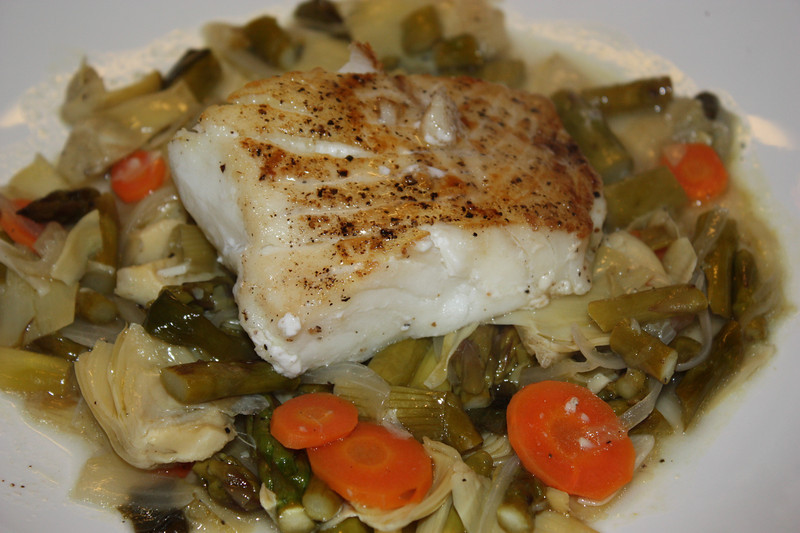 "Pacific Halibut, Grilled Spring Vegetable Barigoule by Sondra Bernstein (from her book ""Plats Du Jour: the girl & the fig's juorney through the seasons in wine country)<br />  <br /> INGREDIENTS:<br /> 18 baby artichokes<br /> Juice of 1 lemon<br /> 2 tablespoons olive oil<br /> 1 buch thin asparagus<br /> 1 bunch small spring onions, cleaned<br /> 6 halibut filets (5 ounces each)<br /> Salt and pepper to taste<br /> 1/2 cup extra-virgin olive oil<br /> 1 small carrot, thinly sliced<br /> 1 small onion, thinly sliced<br /> 2 garlic cloves, thinly sliced<br /> 2 sprigs fresh thyme<br /> 1 bay leaf<br /> 1 cup dry white wine<br /> 1 cup fish stock<br /> 3 tablespoons blended oil (3 parts canola oil and 1 part extra-virgin olive oil)<br /> <br /> DIRECTIONS:<br /> To prepare the artichokes:<br /> Clean the artichokes by removing the top 1/2-inch and the hard outer leaves.  Quarter the artichokes and place them in a large bowl filled with water and the lemon juice.<br /> <br /> To prepare the asparagus:<br /> Preheat a grill<br /> Break off the bottom woody section of the asparagus.  Toss the asparagus and onions in the olive oil and season with salt and pepper.  Grill the asparagus and onions until well browned, about 2 to 4 minutes.  Set aside.<br /> <br /> To prepare the fish:<br /> Preheat the oven to 425 F.<br /> Season the halibut on both sides with salt and pepper.<br /> <br /> Drain the artichokes.  Heat a heavy bottomed saucepan over medium heat.  Add 2 tablespoons of olive oil and saute' the carrots, onion, and garlic until soft, about 5 minutes.  Add the artichokes, thyme, bay leaf, wine, stock, 1 cup water, and the remaining olive oil.  Season, turn the heat to low, and simmer until the artichokes have cooked through, about 10 minutes.<br /> <br /> While the vegetables are cooking, heat the blended oil in a large oven-proof saute' pan over high heat.  Place the halibut in the pan and cook until well browned on one side.  Turn the fish over and place the pan in the oven for 5 to 7 minutes or until the halibut is just cooked through.<br /> <br /> Roughly chop the asparagus and spring onions and add them to the vegetable mixture (the barigoule).  Cook for 2 more minutes.<br /> <br /> To serve:<br /> Divide the barigoule equally among 6 bowls, top with a piece of halibut, and serve immediately.<br /> <br /> JOHN'S NOTE:<br /> Again, another terrific recipe from that book.  Not too much hassle, but a really elegant dish."
