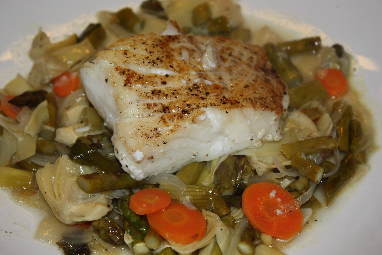 """Pacific Halibut, Grilled Spring Vegetable Barigoule by Sondra Bernstein (from her book """"Plats Du Jour: the girl & the fig's juorney through the seasons in wine country)<br />  <br /> INGREDIENTS:<br /> 18 baby artichokes<br /> Juice of 1 lemon<br /> 2 tablespoons olive oil<br /> 1 buch thin asparagus<br /> 1 bunch small spring onions, cleaned<br /> 6 halibut filets (5 ounces each)<br /> Salt and pepper to taste<br /> 1/2 cup extra-virgin olive oil<br /> 1 small carrot, thinly sliced<br /> 1 small onion, thinly sliced<br /> 2 garlic cloves, thinly sliced<br /> 2 sprigs fresh thyme<br /> 1 bay leaf<br /> 1 cup dry white wine<br /> 1 cup fish stock<br /> 3 tablespoons blended oil (3 parts canola oil and 1 part extra-virgin olive oil)<br /> <br /> DIRECTIONS:<br /> To prepare the artichokes:<br /> Clean the artichokes by removing the top 1/2-inch and the hard outer leaves.  Quarter the artichokes and place them in a large bowl filled with water and the lemon juice.<br /> <br /> To prepare the asparagus:<br /> Preheat a grill<br /> Break off the bottom woody section of the asparagus.  Toss the asparagus and onions in the olive oil and season with salt and pepper.  Grill the asparagus and onions until well browned, about 2 to 4 minutes.  Set aside.<br /> <br /> To prepare the fish:<br /> Preheat the oven to 425 F.<br /> Season the halibut on both sides with salt and pepper.<br /> <br /> Drain the artichokes.  Heat a heavy bottomed saucepan over medium heat.  Add 2 tablespoons of olive oil and saute' the carrots, onion, and garlic until soft, about 5 minutes.  Add the artichokes, thyme, bay leaf, wine, stock, 1 cup water, and the remaining olive oil.  Season, turn the heat to low, and simmer until the artichokes have cooked through, about 10 minutes.<br /> <br /> While the vegetables are cooking, heat the blended oil in a large oven-proof saute' pan over high heat.  Place the halibut in the pan and cook until well browned on one side.  Turn the fish over and place the pan """