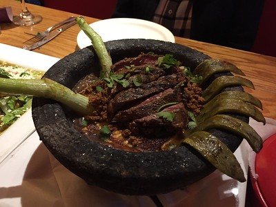 Molkajete - hot lava bowl (molcajete) filled with skirt steak, black beans, homemade sauce, cactus pedals, beef chorizo, onions and panela cheese. Served w/tortillas.