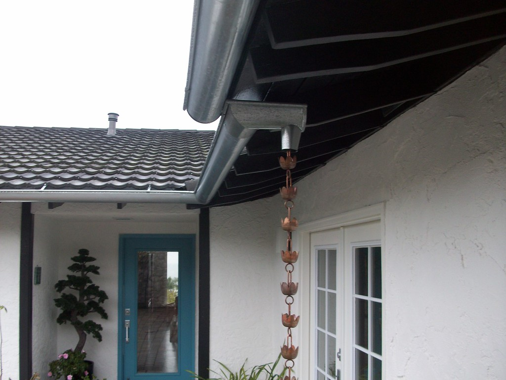 "These are 6"" galvanized steel half round gutters with a copper rain chain on Coronado Island, San Diego.<br /> <br /> We offer soldering as an option on steel gutters. Copper gutters are hand cut, soldered and a strict fastener discipline is maintained with only non-ferrous fasteners used."