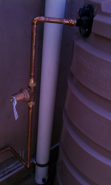 """This shows the rear first flush device ( a normal top fill configuration ) and the city water feed for the tanks. When the tanks are nearing empty the float switch activates and supplies enough city water to the tank to power the irrigation. The brass fitting is a pressure regulator.<br /> <br /> <br /> <br />  <a href=""""http://www.rain-watersystems.com"""">http://www.rain-watersystems.com</a>"""