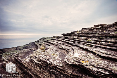 stunning striations on a lichen-encrusted shattered rock face above a rarely-calm sea on the east of orkney mainland 2012 corinne fudge photography