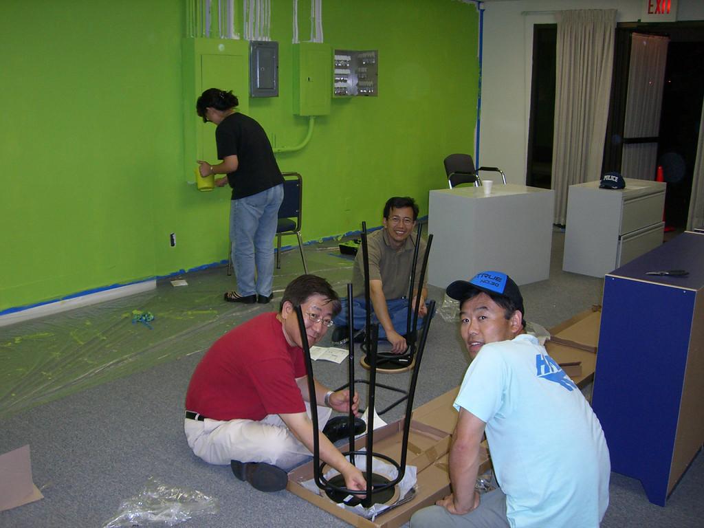 Woman paints - Men assemble furniture
