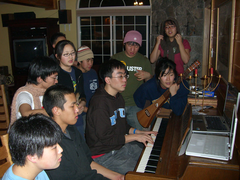 2005 12 27 Tue - Youth Group singing praise around the piano in the cabin 7