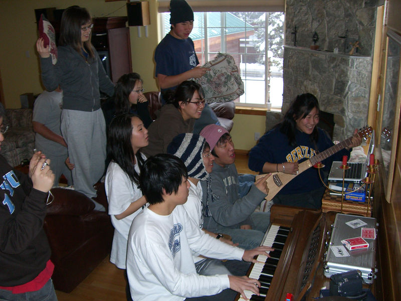 2005 12 27 Tue - Youth Group singing praise around the piano in the cabin 3