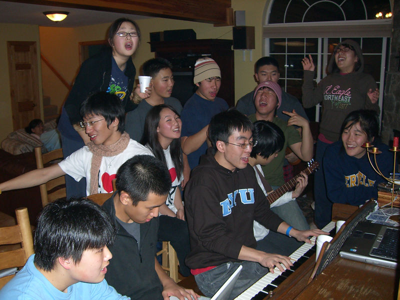 2005 12 27 Tue - Youth Group singing praise around the piano in the cabin 6 - divas and divos