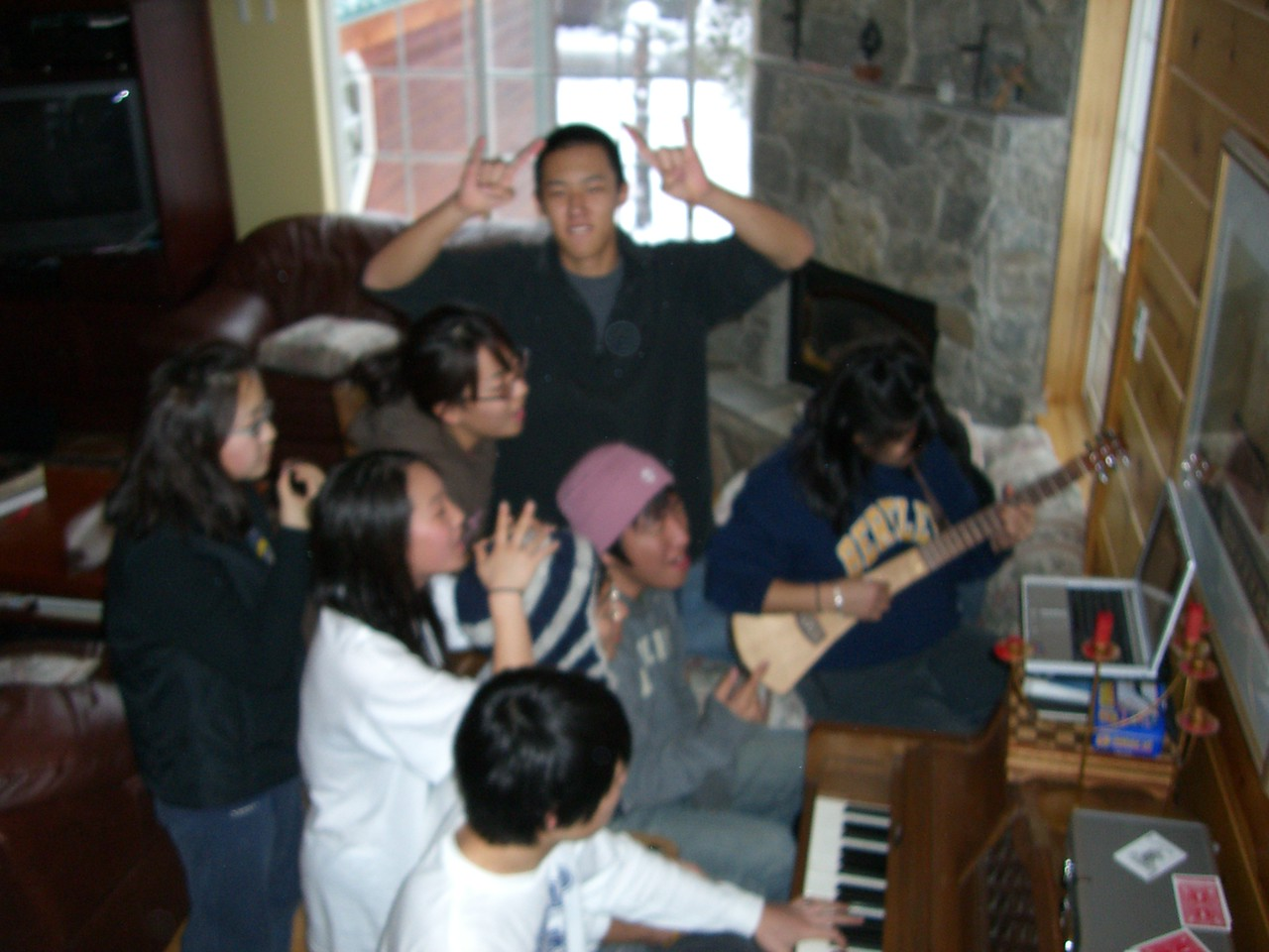 2005 12 27 Tue - Youth Group singing praise around the piano in the cabin 1 - blurry