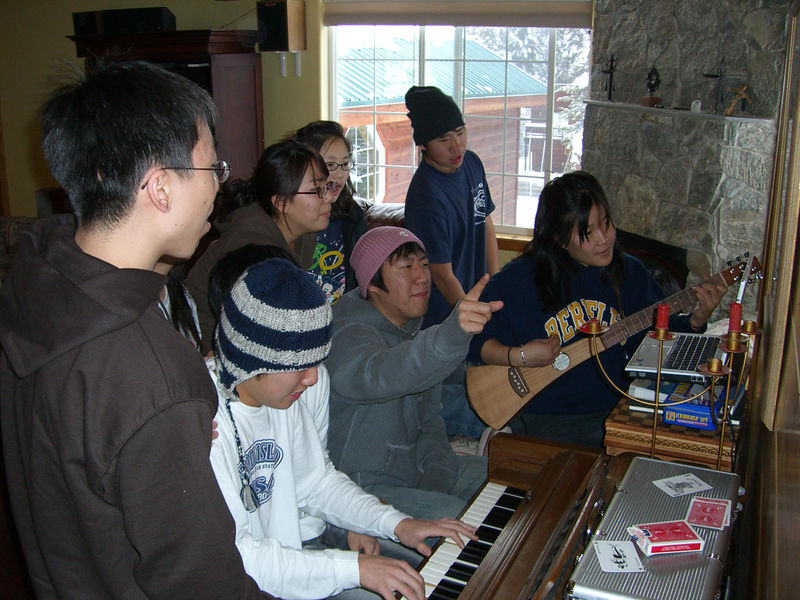 2005 12 27 Tue - Youth Group singing praise around the piano in the cabin 4 - Kirk Kim