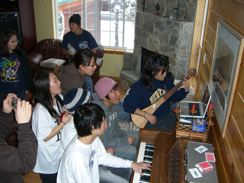 2005 12 27 Tue - Youth Group singing praise around the piano in the cabin 2