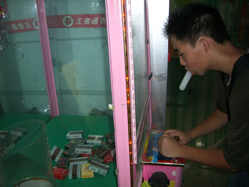 2006 07 22 Sat - Philip Lee plays crane machine for cigarettes