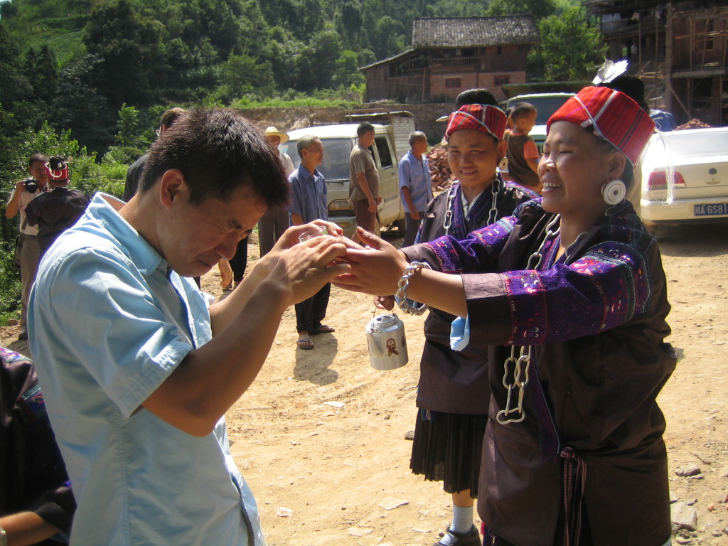 2006 07 30 Sun - Miao village - Welcoming party offers sake to a cringing Nhat Huynh