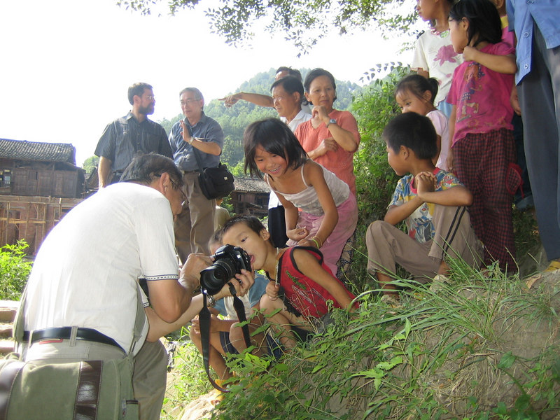 2006 07 30 Sun - Miao village - Joe Ong amazes children by showing their pictures on his dig cam