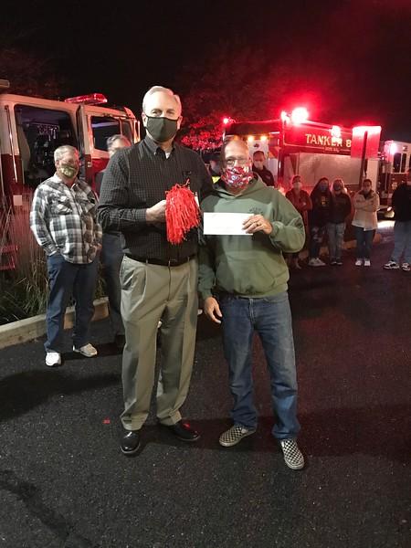 John Hendrickson presenting check to fire chief
