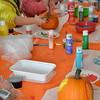 volunteers help children decorate pumpkins