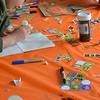 Volunteers help children decorate trick or treat bags