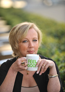 Corporate portrait of Dragon Deborah Meaden by London Bridge relaxing with a mug of coffee saying Feel good