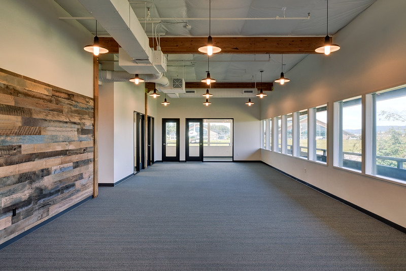 Open office area.  TV monitor wall at left utilizes re-purposed barn wood.