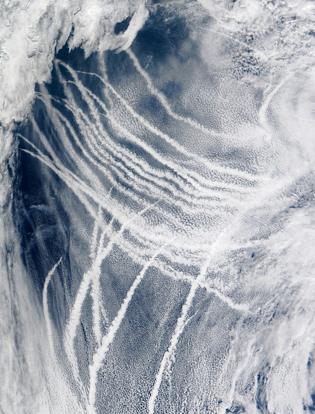 04 Mar 2009 --- They may look like airplane contrails, but the streaky clouds shown in this photo-like image formed around the exhaust left in the wake of ships traveling Northern Pacific Ocean, just south of Alaska. All clouds form when water molecules coalesce onto tiny particles in the atmosphere. The particles can be natural things like dust or sea salt, but they can also be aerosols emitted by human activity. With only the water's surface to influence it, air over the ocean tends to be uniform, often resulting in flat sheets of clouds that cover a wide area. When ships introduce new particles into the air by pumping out a stream of exhaust, water molecules readily cling to the particles, creating long clouds called ship tracks that trail behind a ship. Jeff Schmaltz, MODIS Land Rapid Response Team, NASA GSFC --- Image by © NASA/Corbis