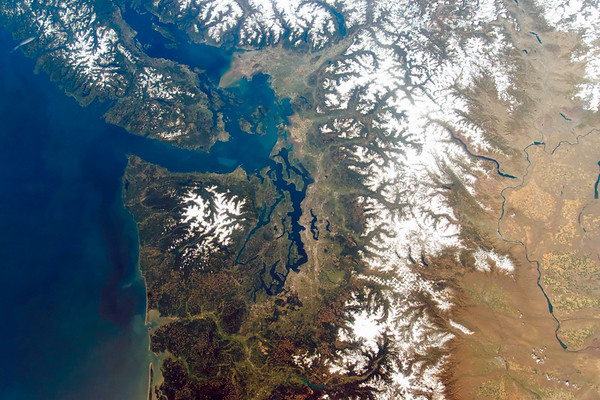 Washington State and the Puget Sound as seen from the International Space Station on a cloudless day. The snow-capped Cascades run from top to bottom; the large white blob of Mount Rainier is below a checkerboard pattern of clear cuts. The upper Columbia river runs through dryer eastern Washington on the right. Seattle is dead center; to the left is the Puget Sound and the Olympic Peninsula. Vancouver Island, Victoria, and the city of Vancouver are in the upper left. --- Image by © NASA - digital version copyright/Science Faction/Corbis