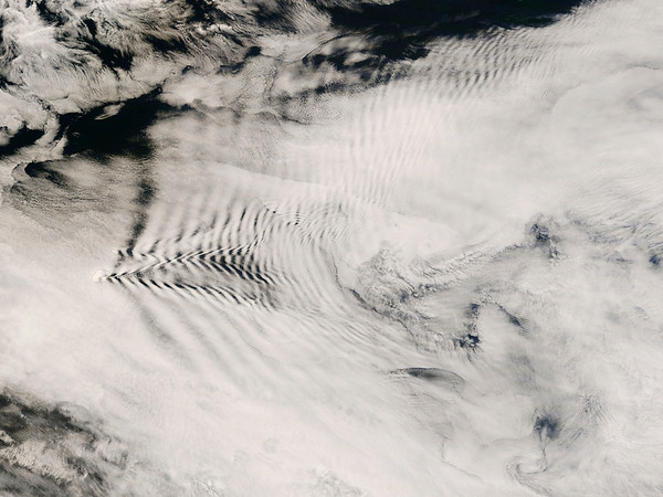 """16 Oct 2008 --- The cloud patterns seen in this image, captured by the MODIS on the Terra satellite on October 16, 2008, are called """"ship-wave-shaped clouds"""". They are called this because they resemble ship waves (or """"Kelvin ship waves""""), which are the V-shaped wakes left by moving objects, such as ships or even ducks. In this case, the cloud patterns were caused by the Prince Edward Islands in the South Indian Ocean (not to be confused with the Prince Edward Island in Canada). As the wind flows past the islands, it is swept around and over it leaving a wake similar to that of a ship-- hence the name """"ship-wave-shaped"""" clouds. Wind behaves like a fluid; when it encounters an obstacle, it must move around it, leaving behind a wake (like Von Karmann vortices), or a visible wave pattern. --- Image by © NASA/Corbis"""
