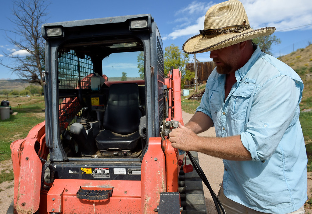 . Best LONGMONT, CO - AUG. 30, 2018:  Adam Tveten connects hydraulic lines to his skid steer Aug. 30. Tveten purchased the skid steer with state grant money to repair the flood damage to his ranch along the Little Thompson River north of Longmont. (Photo by Lewis Geyer/Staff Photographer)
