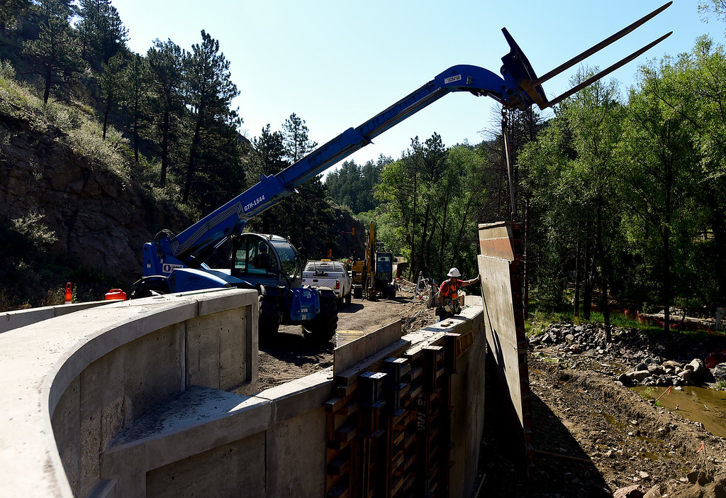 . BOULDER COUNTY, CO - AUGUST 9: Carpenter John Ballinger, of SEMA Construction, helps a material handler operator lift a concrete form out off a wall near Logan Mill Road and Fourmile Canyon Drive in Boulder County on Aug. 9, 2018. (Photo by Matthew Jonas/Staff Photographer)