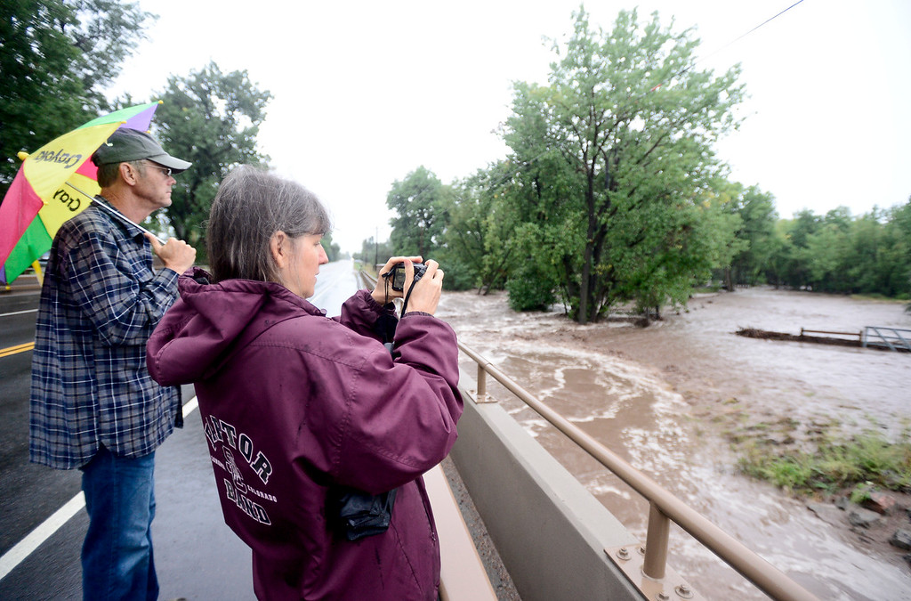 . Carolyn Stefansky and Mark Stefansky watch as the Lefthand Creek floods nearby land from the bridge at North 63rd Street, Thursday, Sept. 12, 2013, near Niwot. (Matthew Jonas/Times-Call)