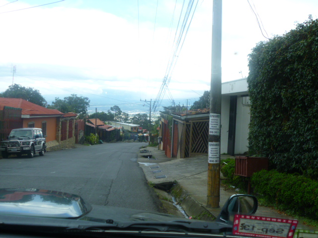Coming from the main street in Escazu (the one that goes up the hill towards San Antonio de Escazu - from behind the church) it's about 8 blocks up.  The bus stops about 50 meters/1/2 block from the house.