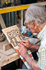 An elderly gentleman wood carving in a craft shop in the village of Sarchii, Costa Rica, Central America.