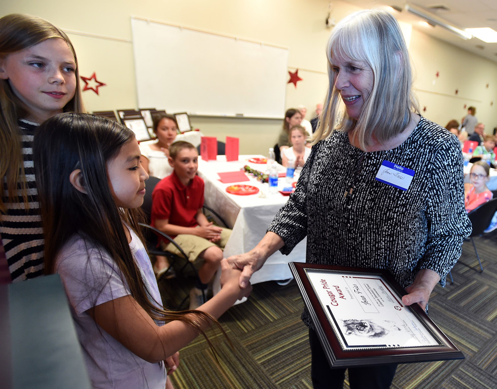 . Joan Fries, right, receives her Cougar Award from Abby Brende, left, and Paris Xiong. The Cougar Pride Awards is an annual event, created by students a Lafayette Elementary,  to honor school retirees in the Lafayette area.  Cliff Grassmick  Staff Photographer May 17, 2017