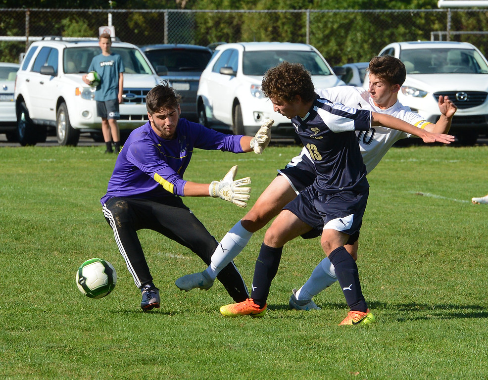 . North\'s Justin Scharf (10) tries to get ball by South GK Drew Bresnan (00) and Hawks defender Paul Chorobski (13).