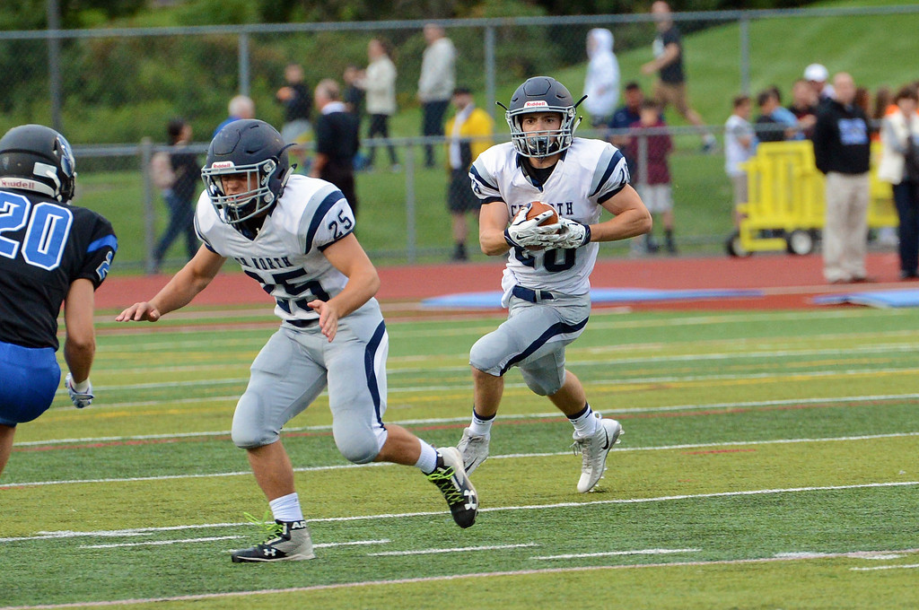 . Mike Welde (28) follows Dillon Sheehy\'s (25) block.