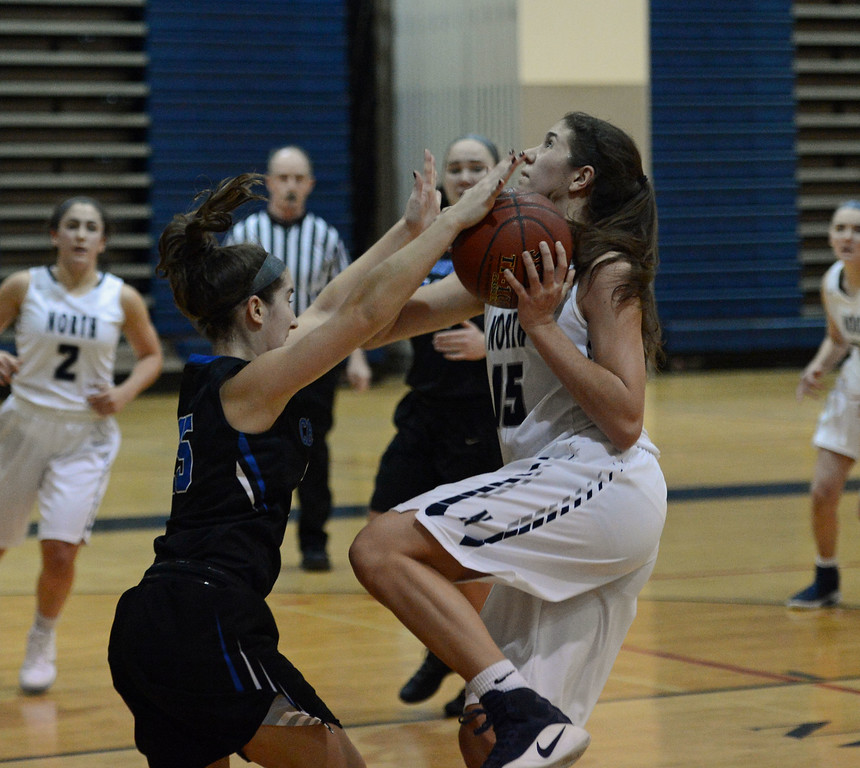 . Dana Bandurick (15) is fouled on the way to the basket.