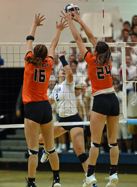 . Maddy Moore (2) finesses the ball by Shelby Hastings (16) and Elley Torres (24).