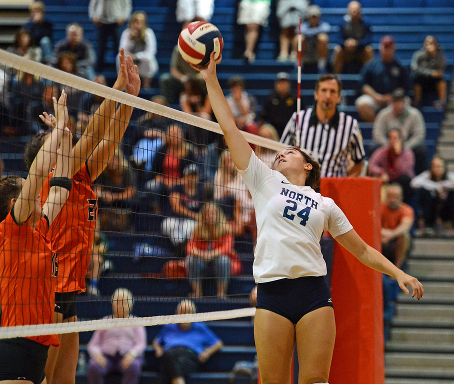 . Sarah Caola (24) finesses the ball over the net.