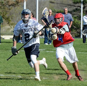 Neshaminy's Adam Schwitter (4) tries to knock ball from Connor McGuigan's (2) stick April 19 at Council Rock North. (photos by John Gleeson)