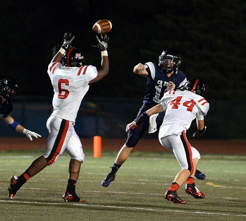 . Council Rock North senior quarterback Evan Devine (#10) fires pass over Taun Evans\' outstretched hands.