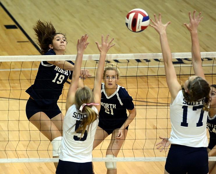 Dana Bandurick (19) slams ball at Celina Varian (5) and Hannah Sullivan (17).