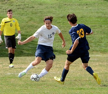 Eric Levine (#5) maneuvers the ball by Eddie Fortescue (33).
