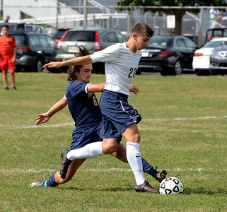 Justin Scharf (#23) beats Tom McHale (6) to the ball.