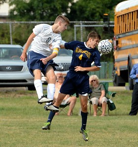 CR North's Grant Bonas (#8) heads ball by Trojans' Justin Ryan (4).
